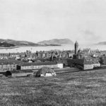 This comprehensive view of Campbeltown, looking eastwards over Glebe Street towards the loch and Davaar Island, was taken from Gallowhill on a long-gone summer's day. The steeple that was then Longrow Church (now the Lorne and Lowland Church), dominates the townscape, and across the loch a ship can be seen on the stocks at Trench Point shipyard. Rows of distillery buildings can be seen behind the hay rucks.