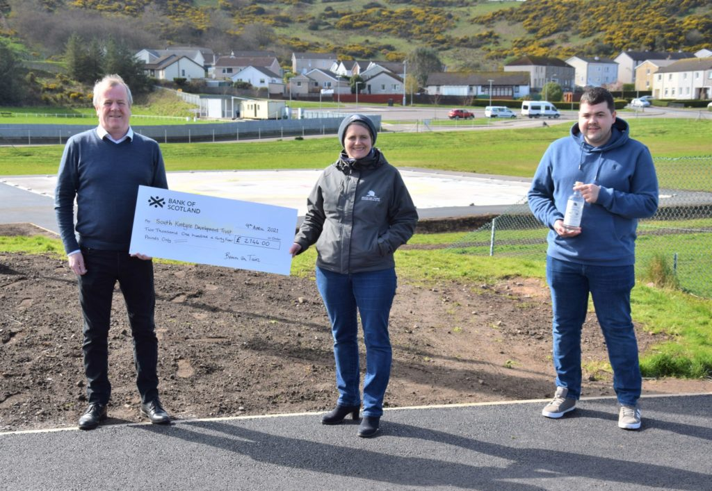 From left: South Kintyre Development Trust manager Eric Spence, Beinn an Tuirc Distillers director Emma Macalister Hall and highest bidder Lewis Nelson.