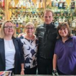 Actor Sam Heughan behind the Ardshiel Hotel bar with office manager Amanda Grant and owners Flora Grant and Marion MacKinnon.
