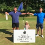 Iain Macalister celebrates his Par 3 Open win with his granddaughter Willow and club captain Kenny MacFarlane.