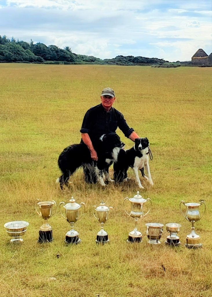 Alex MacCuish and his two dogs with his haul of Kintyre trophies.