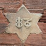 Which building features this decorative date stone?