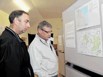 PLANNING AHEAD:  Local residents  Alistair McLeod, left,  and Brian Tait study the maps of the proposed windfarm on Mormond Hill