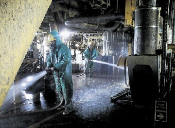 DANGEROUS:  Workers carry out cleaning operations  on the  Elgin wellhead platform ahead of attempts to kill the leaking well