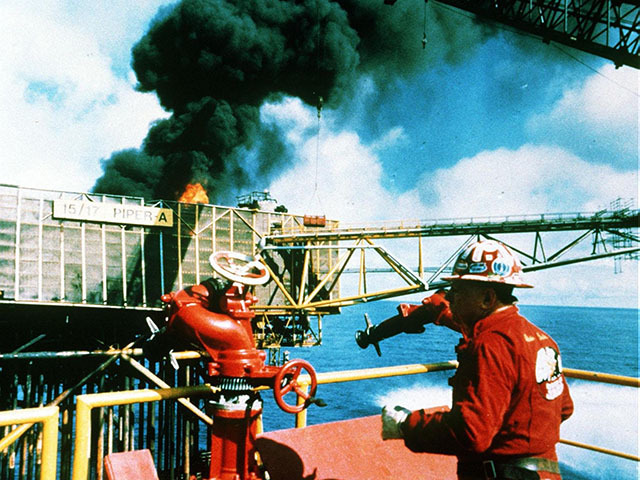 Texan expert fire fighter Red Adair on the still-burning Piper Alpha offshore platform, before he was forced to retreat by a combination of a surge of flames from one of the wells and worsening weather.