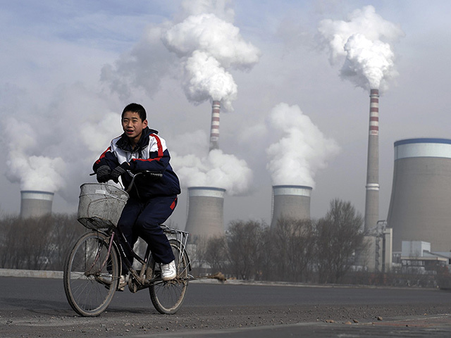 EMISSIONS: A Chinese boy cycles past the cooling towers of a coal-fired power plant in China