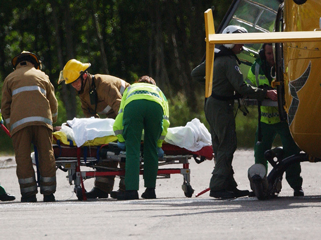 Paramedics and firefighters comfort a victim coming from medevac helicopter