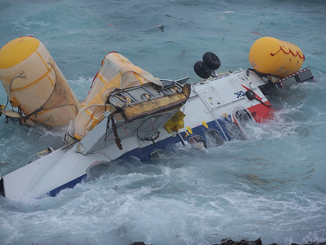 Wreckage of the helicopter after the August crash which killed four people is buffeted by the surf off the Shetland mainland