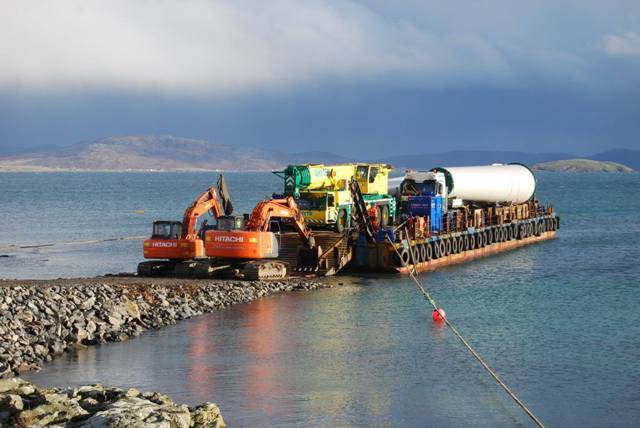 A barge transports part of the turbine to the site