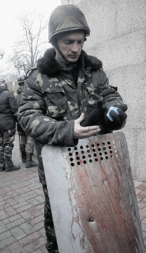 HELL: An activist holds a shield covered with the blood of his comrade killed in clashes with police in Kiev's Independence Square, the epicentre of the country's current unrest