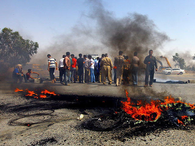 Iraqi Kurds block a road during a demonstration against the fuel crisis in Irbil, Iraq, on June 29, 2014.