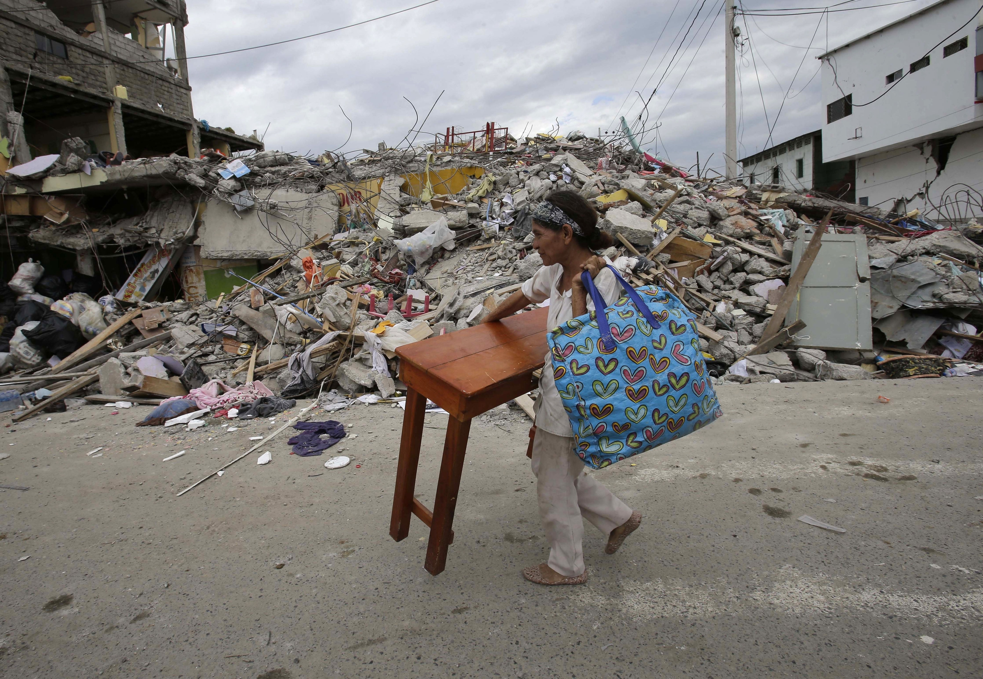 A woman carries a table through the street after an earthquake in Pedernales, Ecuador, Sunday, April 17, 2016. Rescuers pulled survivors from the rubble Sunday after the strongest earthquake to hit Ecuador in decades flattened buildings and buckled highways along its Pacific coast on Saturday. The magnitude-7.8 quake killed hundreds of people.