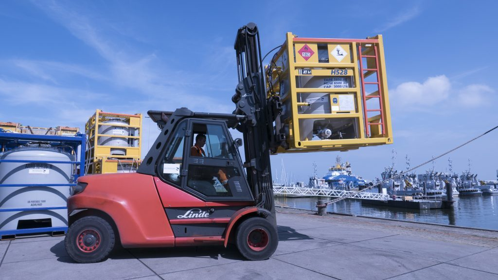 An offshore transport fuel tank being moved in a forklift.