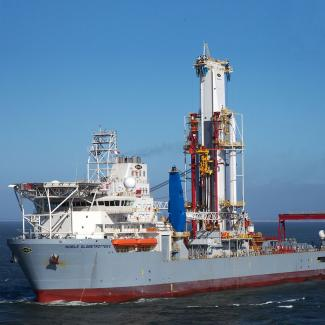 A rig with light grey hull against blue sky