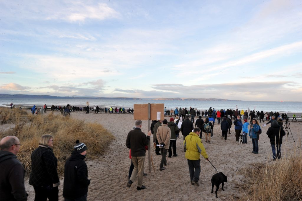 Protest at Nairn against ship to ship oil transfers in the Moray Firth.  A long line of over 500 protesters gather on the beach.