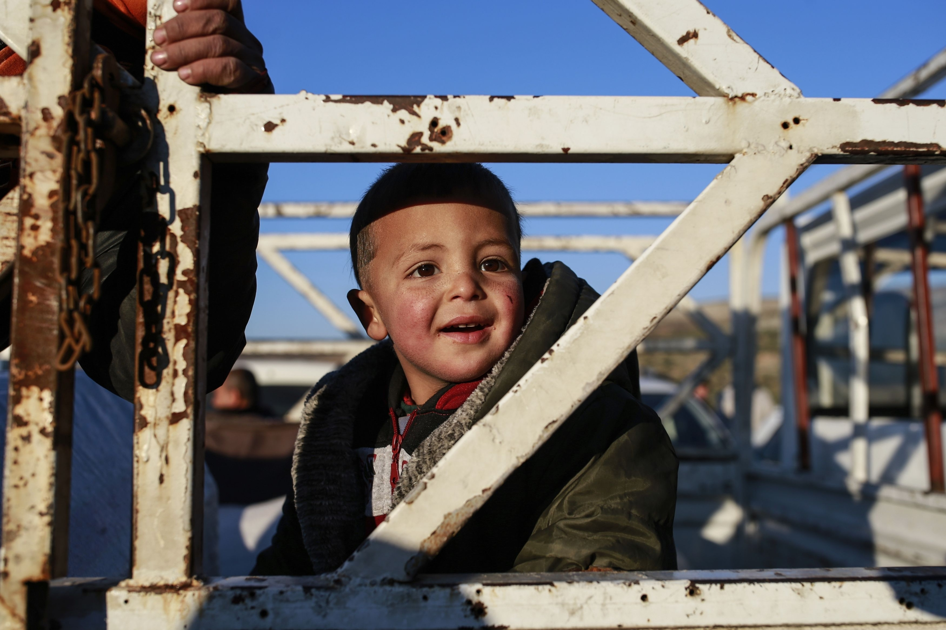 A Syrian child smiles as he is driven away after he and other members of the family crossed into Turkey at the Cilvegozu border gate with Syria, near Hatay, southeastern Turkey, Sunday, Dec, 18, 2016. Several people were able to cross into Turkey after they managed to leave the embattled Syrian city during the ceasefire