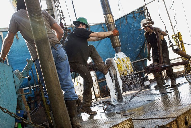 Workers connect drill bits and drill collars, used to extract natural petroleum, on Endeavor Energy Resources LP's Big Dog Drilling Rig 22 in the Permian basin outside of Midland, Texas. Photographer: Brittany Sowacke/Bloomberg