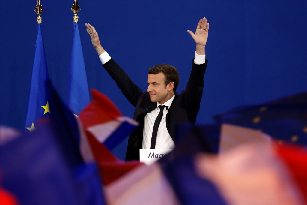 Emmanuel Macron puts his arms up amid French flags