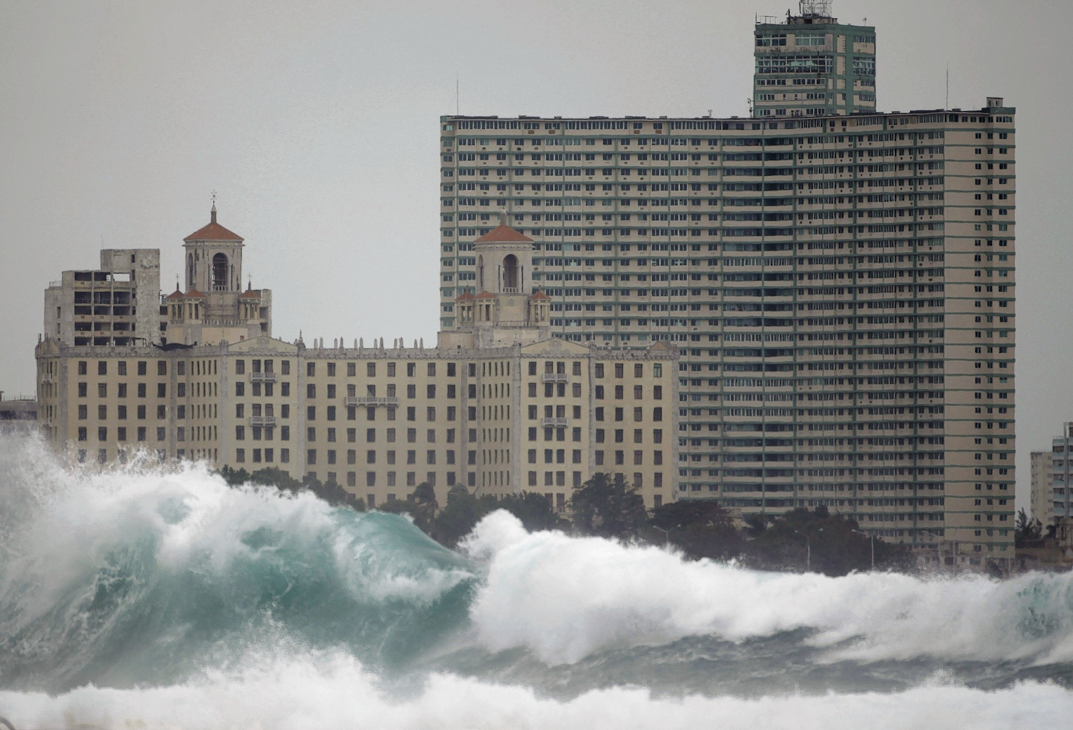 The National hotel, left, and Riviera hotel stand behind waves hitting Havana's Malecon seafront in Cuba, Monday Dec. 13, 2010.
