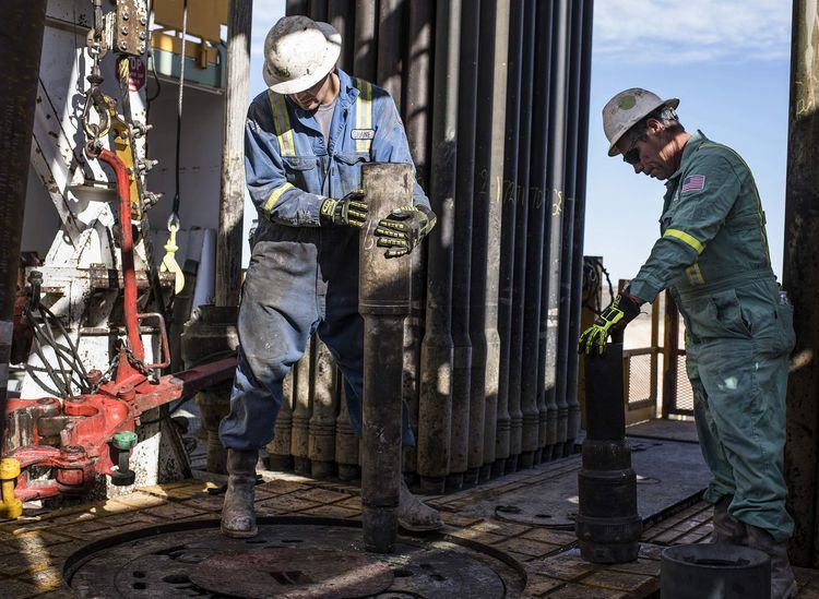 Precision Drilling oil rig operators install a bit guide on the floor of a Royal Dutch Shell Plc oil rig near Mentone, Texas. Photographer: Matthew Busch/Bloomberg
