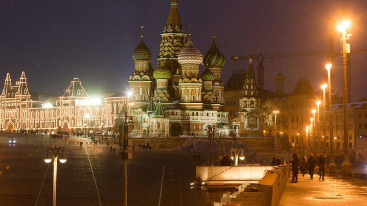 The GUM luxury department store, left, sits illuminated at night on Red Square near St. Basil's cathedral in Moscow, Russia, on Wednesday, Nov. 9, 2016. Russia is realistic about limits on the prospects for an immediate improvement in relations with the U.S. after President-elect Donald Trump takes office, according to President Vladimir Putins spokesman. Photographer: Andrey Rudakov/Bloomberg
