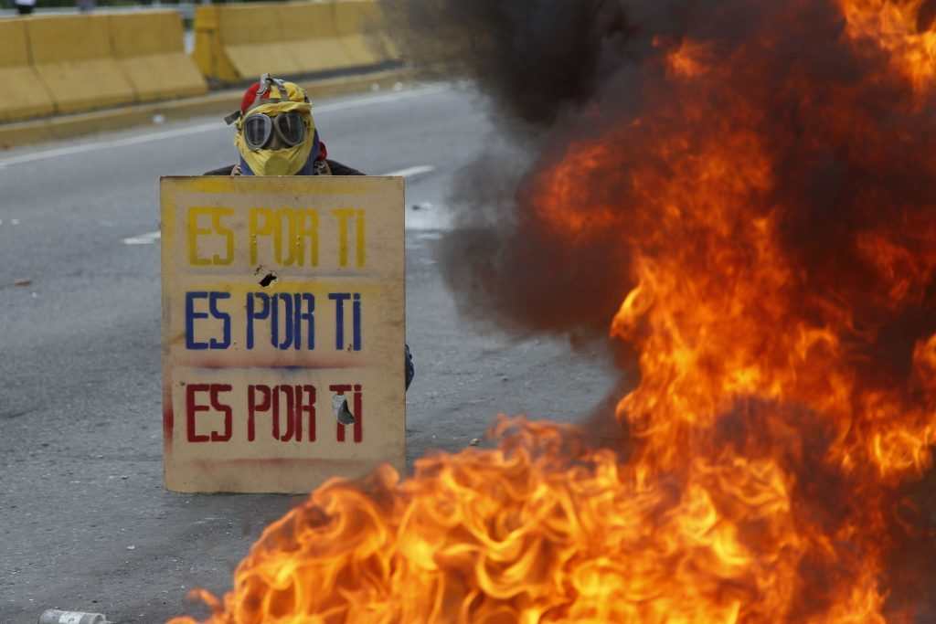 """A demonstrator holds a sign that doubles a shield that reads in Spanish """"It's for you,"""" during a national sit-in against President Nicolas Maduro, in Caracas, Venezuela, Monday, May 15, 2017."""