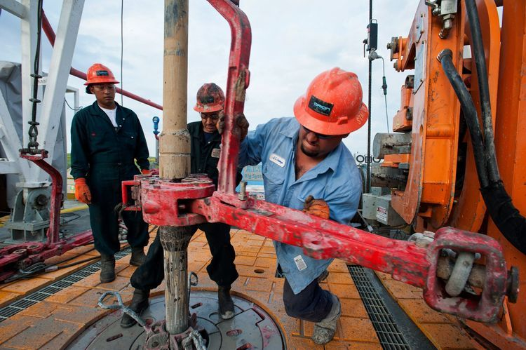 Floor hands David Vannapha, left, Mario Ramos, center, and Jose Garza make a pipe connection on the drill string on the Orion Perseus drilling rig near Encinal in Webb County, Texas, U.S. Photographer: Eddie Seal/Bloomberg