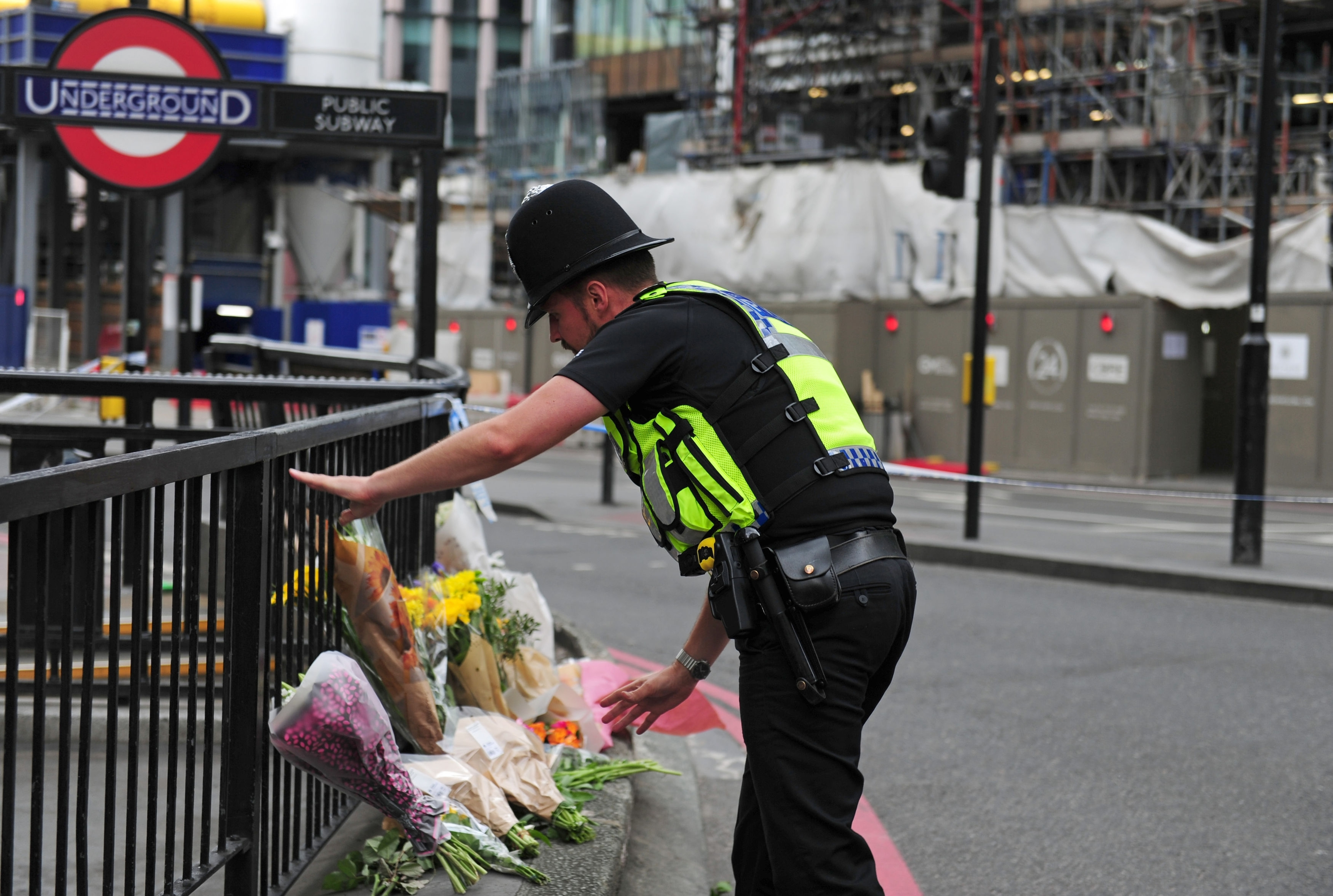A police officer lays flowers passed to him by members of the public on the north side of London Bridge following the terrorist incident.