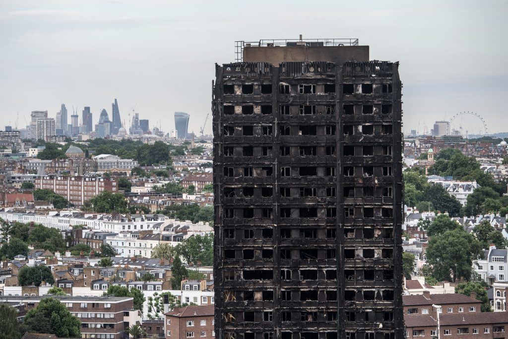 The City of London skyline is seen behind the remains of Grenfell Tower on June 26, 2017 in London, England. 79 people have been confirmed dead and dozens still missing after the 24 storey residential Grenfell Tower block was engulfed in flames in the early hours of June 14, 2017.