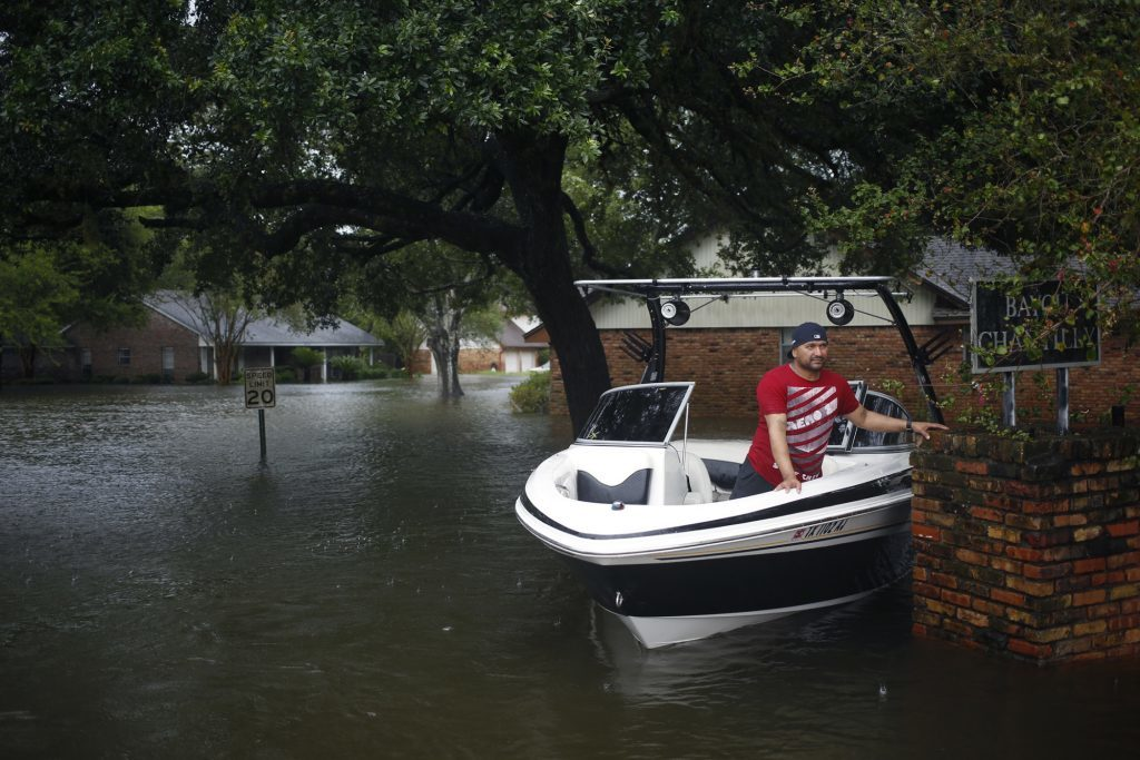 A man waits in a motorboat while making rescues in floodwaters from Hurricane Harvey in Dickinson, Texas, U.S., on Tuesday, Aug. 29, 2017. Estimates for damages caused by Hurricane Harvey are climbing with the storm poised to regain strength in the Gulf of Mexico before crashing back on land. Photographer: Luke Sharrett/Bloomberg