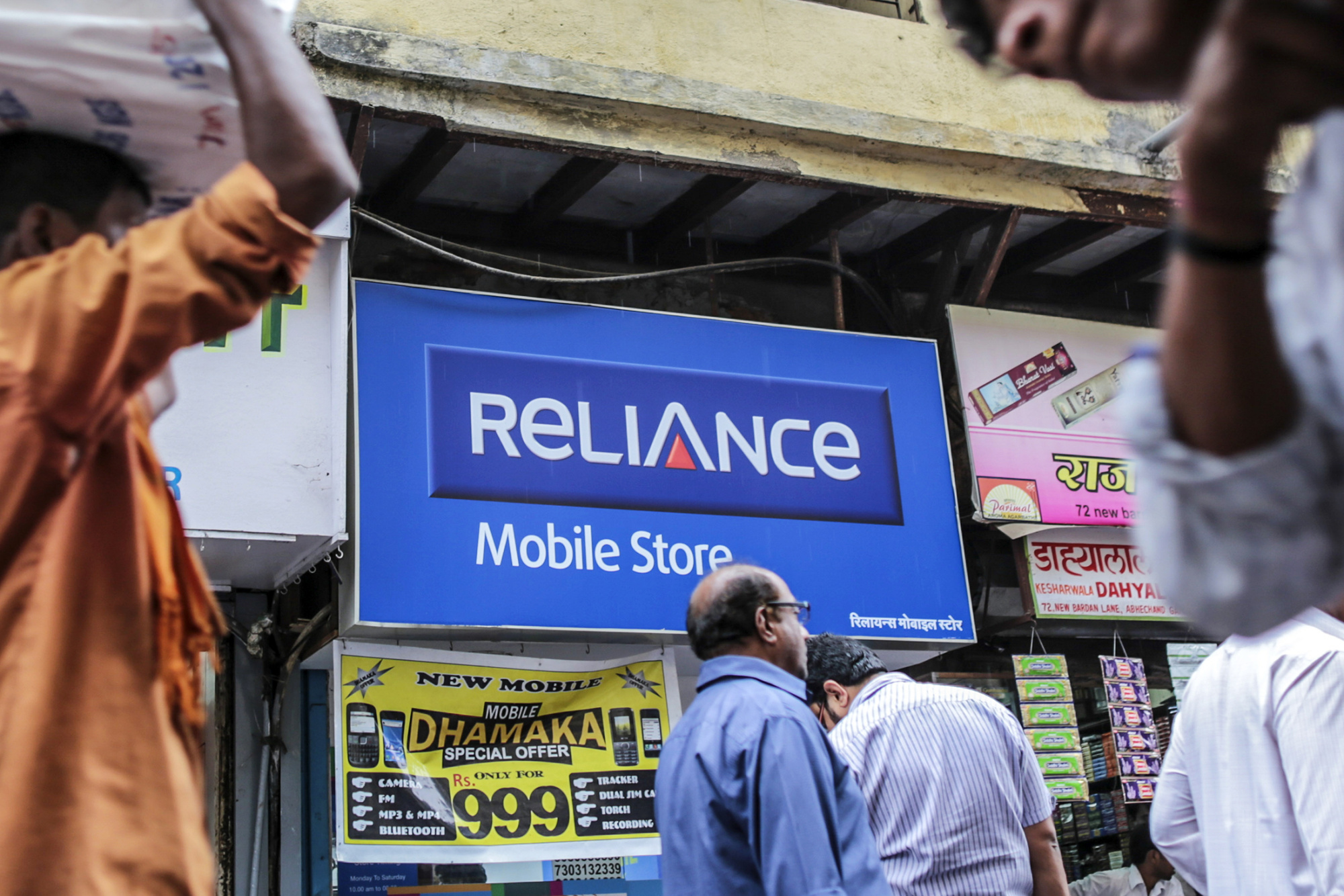 Pedestrians walk past a Reliance Communications Ltd. Mobile Store in Mumbai, India, on Saturday, Feb. 28, 2015. The government auction of telecom wireless spectrum starting March 4 is expected to raise as much as $15.6 billion from service providers including those controlled by billionaires Kumar Mangalam Birla, Sunil Mittal and Anil Ambani, according to ICRA Ltd. Photographer: Dhiraj Singh/Bloomberg