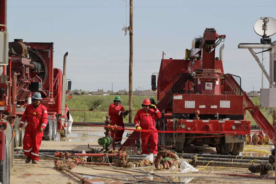 After heavy overnight rains, Halliburton employees look over a Sandcastle at a fracking site operated by Dallas oil company RSP Permian last month in Midland.