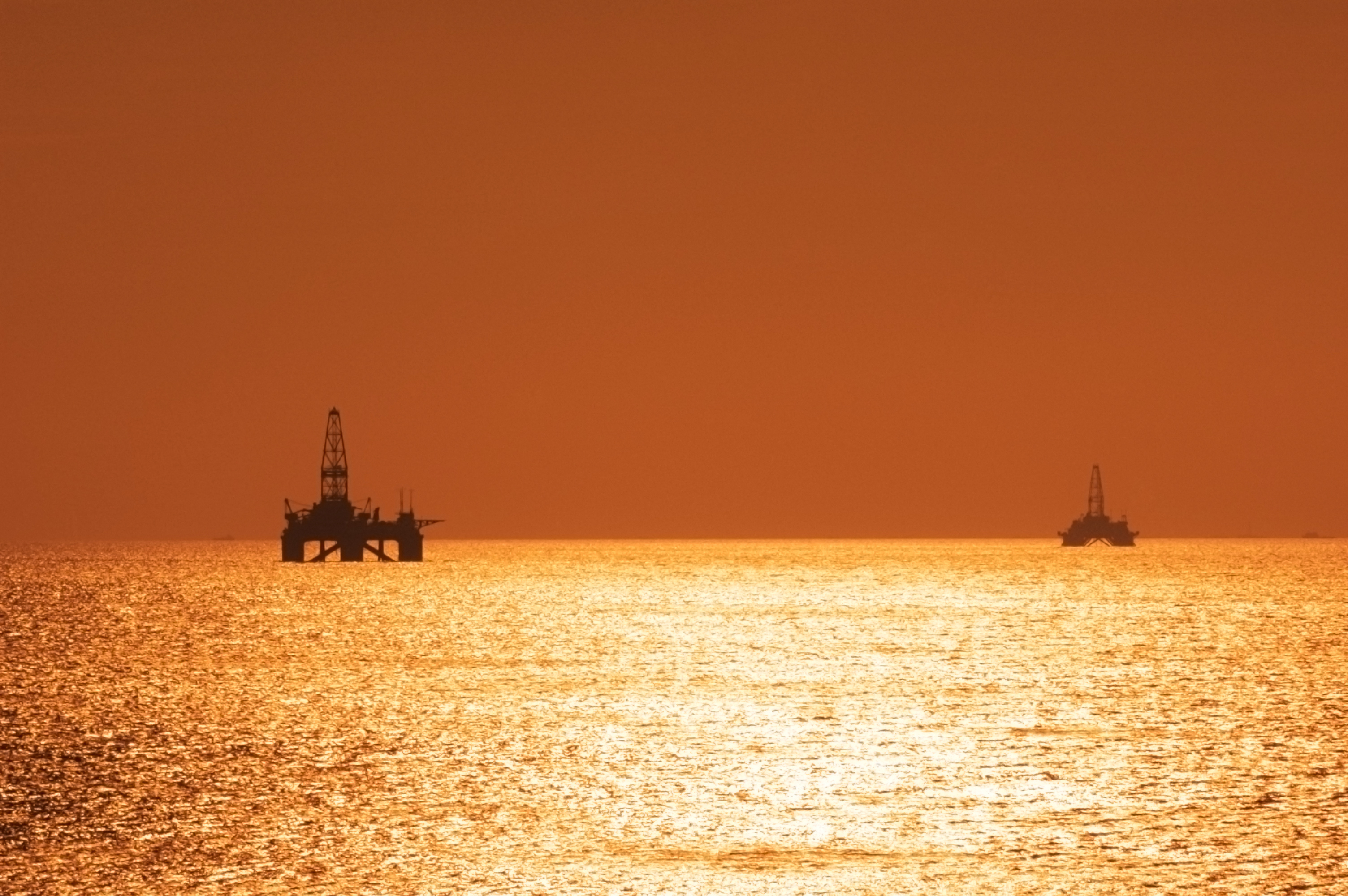 Two offshore oil rigs during sunset in Caspian sea.