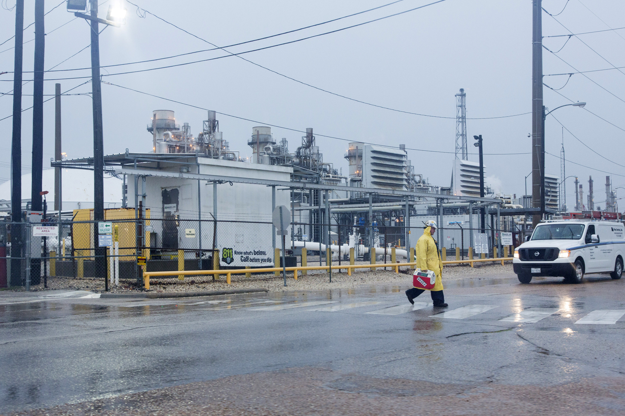 A worker wears rain gear while passing in front of the Marathon Petroleum Corp. refinery ahead of Hurricane Harvey in Texas City, Texas, U.S. Photographer: F. Carter Smith/Bloomberg