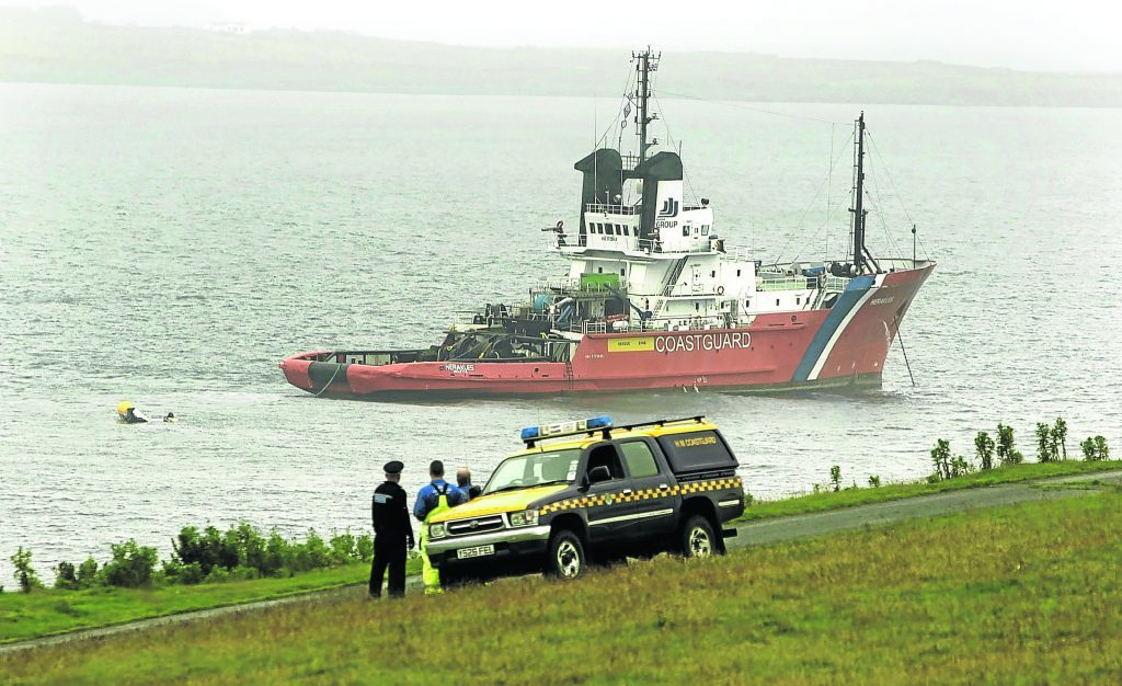 A Coastguard ship at Sumburgh works to recover the helicopter and bodies from the sea