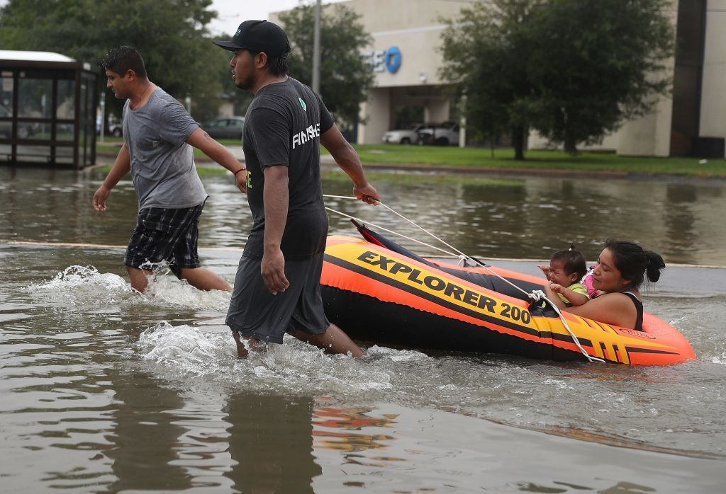 People use a boat to evacuate their home after the area was inundated with flooding from Hurricane Harvey
