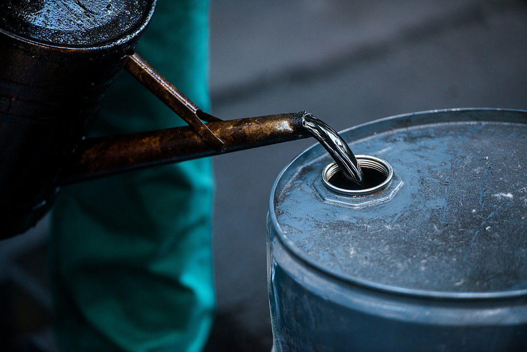 A worker pours liquid oil into a barrel at the delayed coker unit of the Duna oil refinery operated by MOL Hungarian Oil and Gas Plc in Szazhalombatta, Hungary.