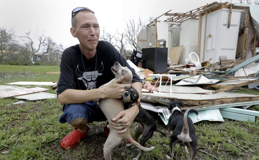 Sam Speights tries to hold back tears while holding his dogs and surveying the damage to his home in the wake of Hurricane Harvey
