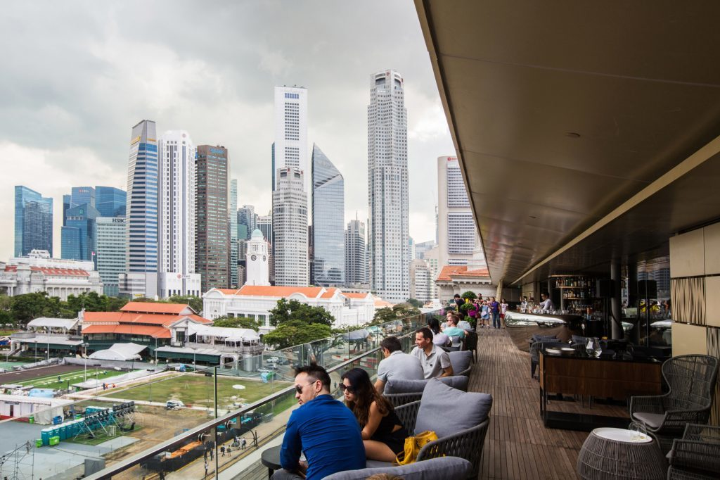 Visitors sit in a cafe at the National Gallery Singapore as commercial buildings stand in the background in Singapore, on Friday, Nov. 27, 2015. Photographer: Nicky Loh/Bloomberg