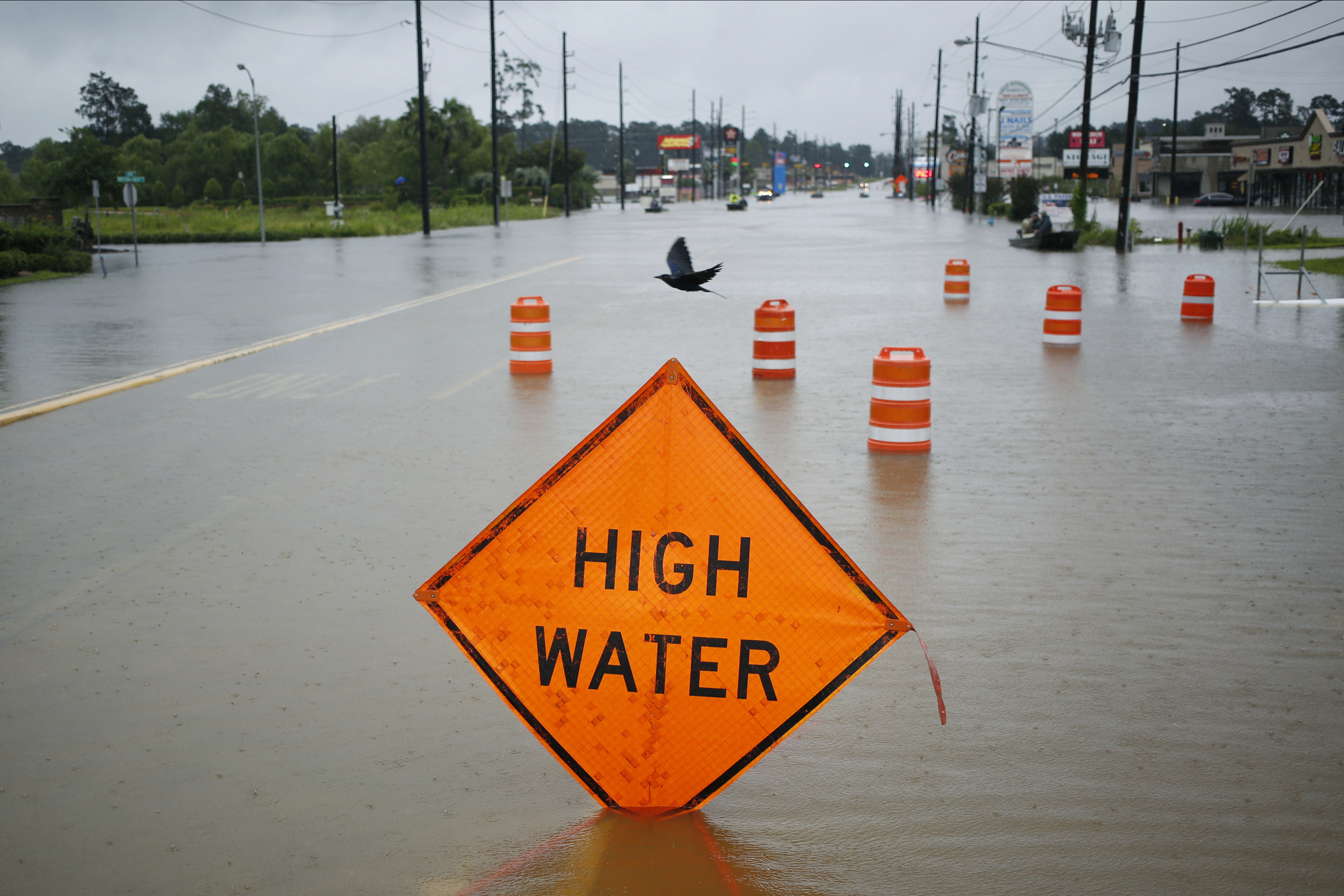 "A ""High Water"" and orange traffic barrels stand in floodwaters from Hurricane Harvey in Spring, Texas, U.S. Photographer: Luke Sharrett/Bloomberg"