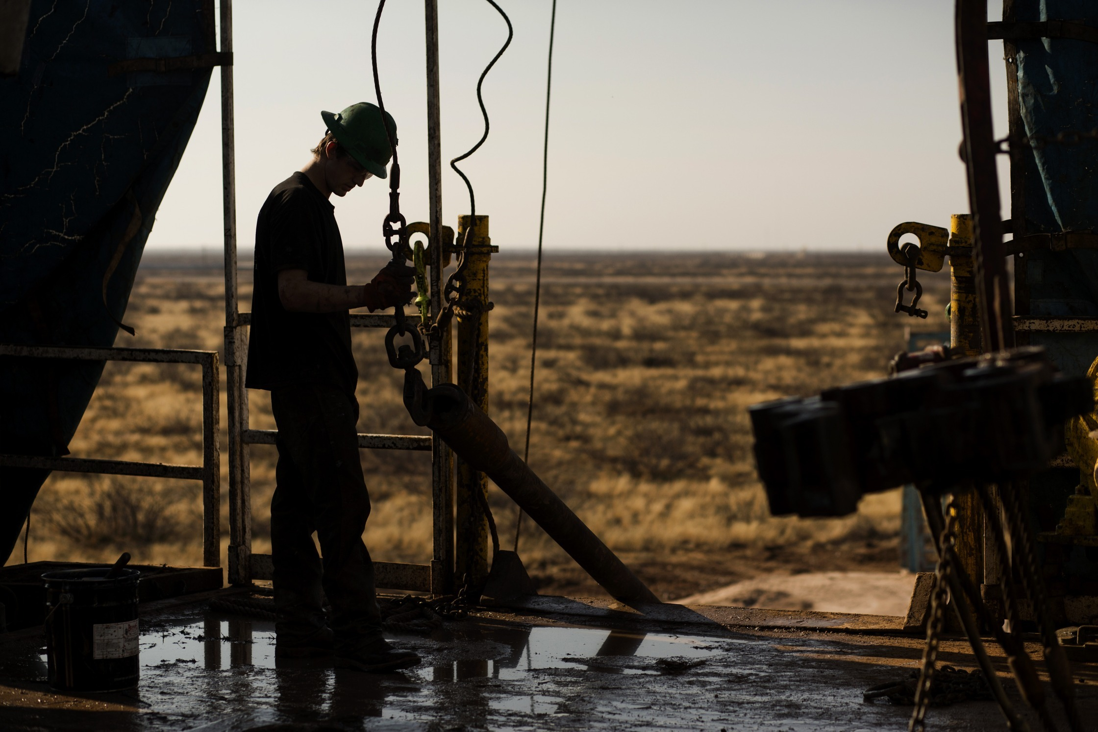 A worker waits to connect a drill bit on Endeavor Energy Resources LP's Big Dog Drilling Rig 22 in the Permian basin outside of Midland, Texas, U.S. Photographer: Brittany Sowacke/Bloomberg