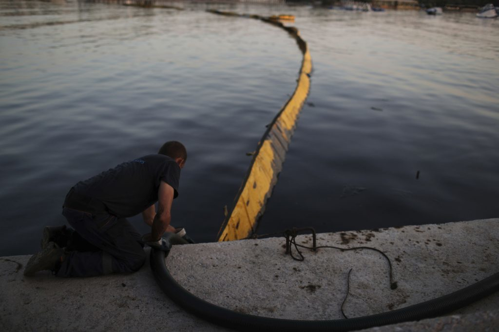 A worker from a cleaning company uses a hose to suck up polluted water from an oil spillage in front of a floating boom in Glyfada, suburb of Athens, on Monday, Sept. 18, 2017. The World Wildlife Fund has filed a lawsuit in Greece over extensive pollution along Athens' coastline following the sinking of a tanker near the country's largest port of Piraeus..