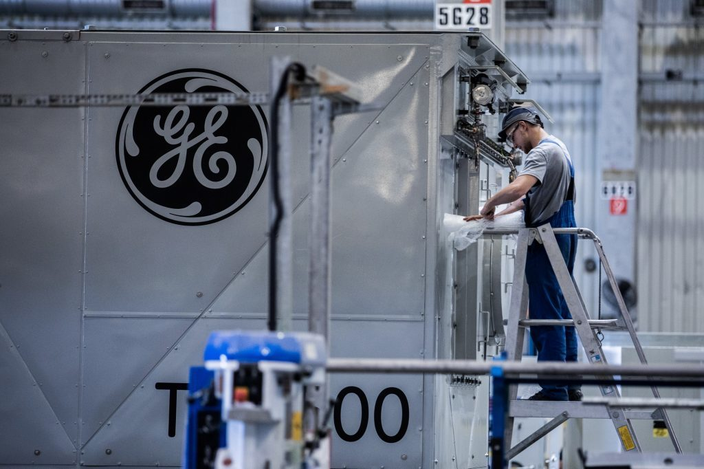 An employee unwraps turbine components inside the General Electric Co. power plant in Veresegyhaz, Hungary. Photographer: Akos Stiller/Bloomberg