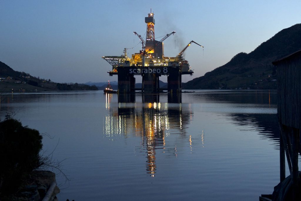The Scarabeo 8 deepwater oil drilling rig stands illuminated at night after being re-fitted at the Westcon AS yard in Olensvag, Norway, on Tuesday, April 3, 2012.  Photographer: Kristian Helgesen/Bloomberg