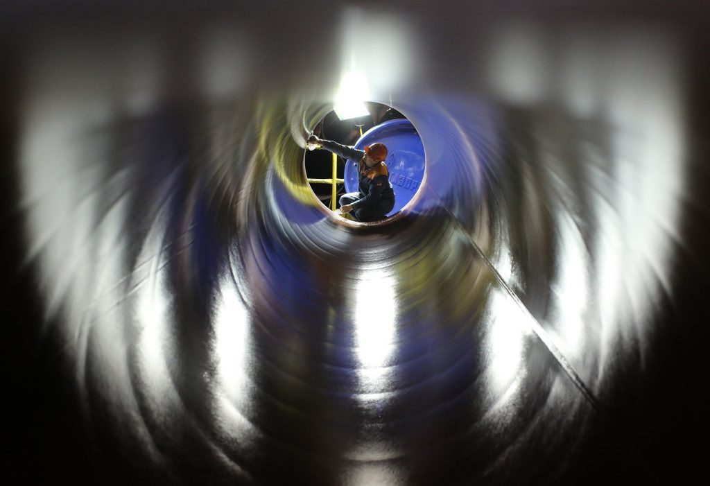 A worker checks the inside of a longitudinally welded large diameter steel pipe for use in oil and gas pipelines in a storage area at the Volzhsky Pipe Plant OJSC, operated by TMK PJSC, in Volzhsky, Russia, on March 30, 2017. Russian pipe producer TMK PJSC expects its U.S. business to recover as higher oil prices and President Donald Trump's trade and infrastructure policies boost demand. Photographer: Andrey Rudakov/Bloomberg