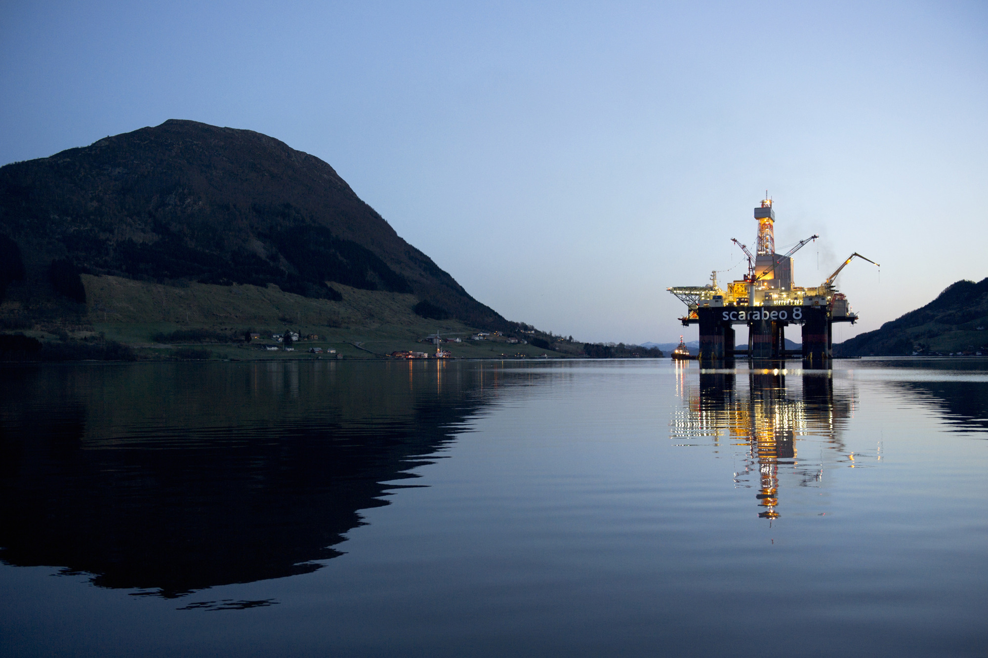The Scarabeo 8 deepwater oil drilling rig, operated by ENI Norge AS, stands illuminated at night after being re-fitted at the Westcon AS yard in Olensvag, Norway. Photographer: Kristian Helgesen/Bloomberg
