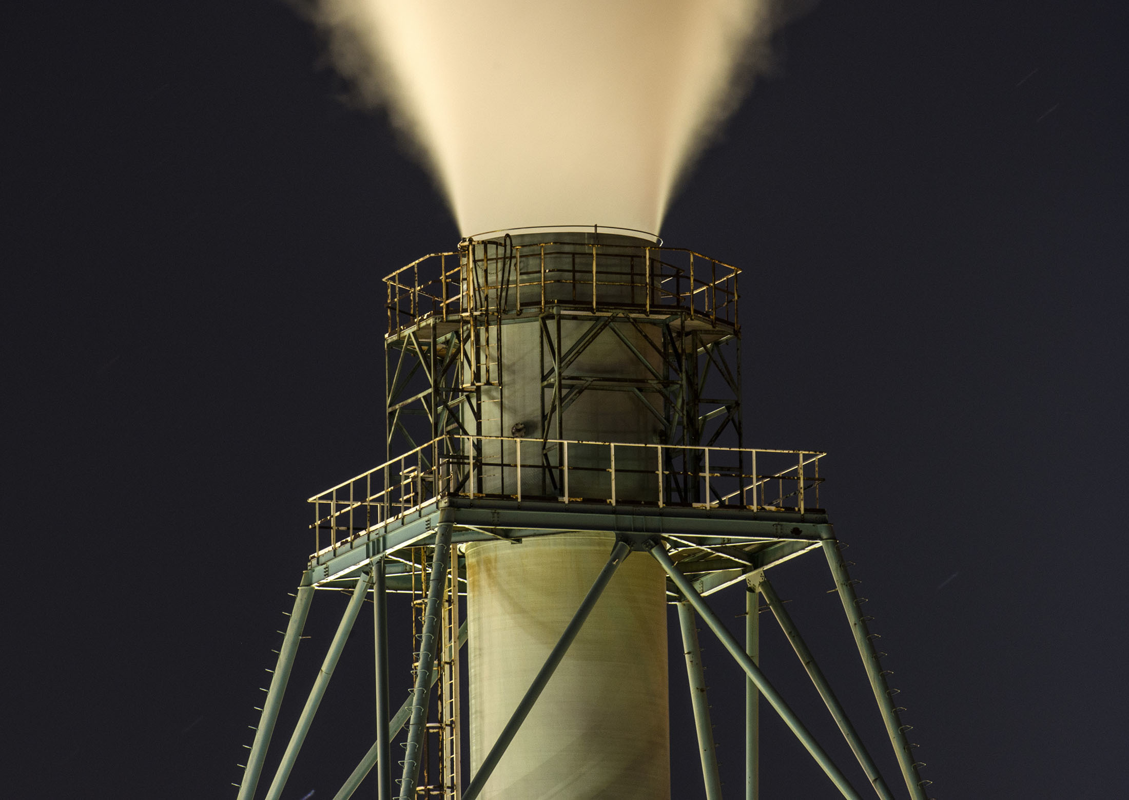 Vapor rises into the sky from a smoke stack at the JXTG Nippon Oil & Energy Corp. Muroran petrochemical plant illuminated at night in Muroran, Japan, on Friday, Oct. 27, 2017. JXTG Holdings Inc., JXTG Nippon Oil & Energy's parent company, is scheduled to announce its second-quarter earnings figures on Nov. 10. Photographer: Eiji Ohashi/Bloomberg