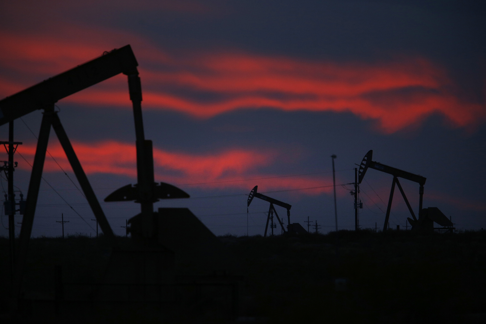 The silhouettes of electric oil pump jacks are seen at dusk in the oil fields surrounding Midland, Texas, U.S. Photographer: Luke Sharrett/Bloomberg