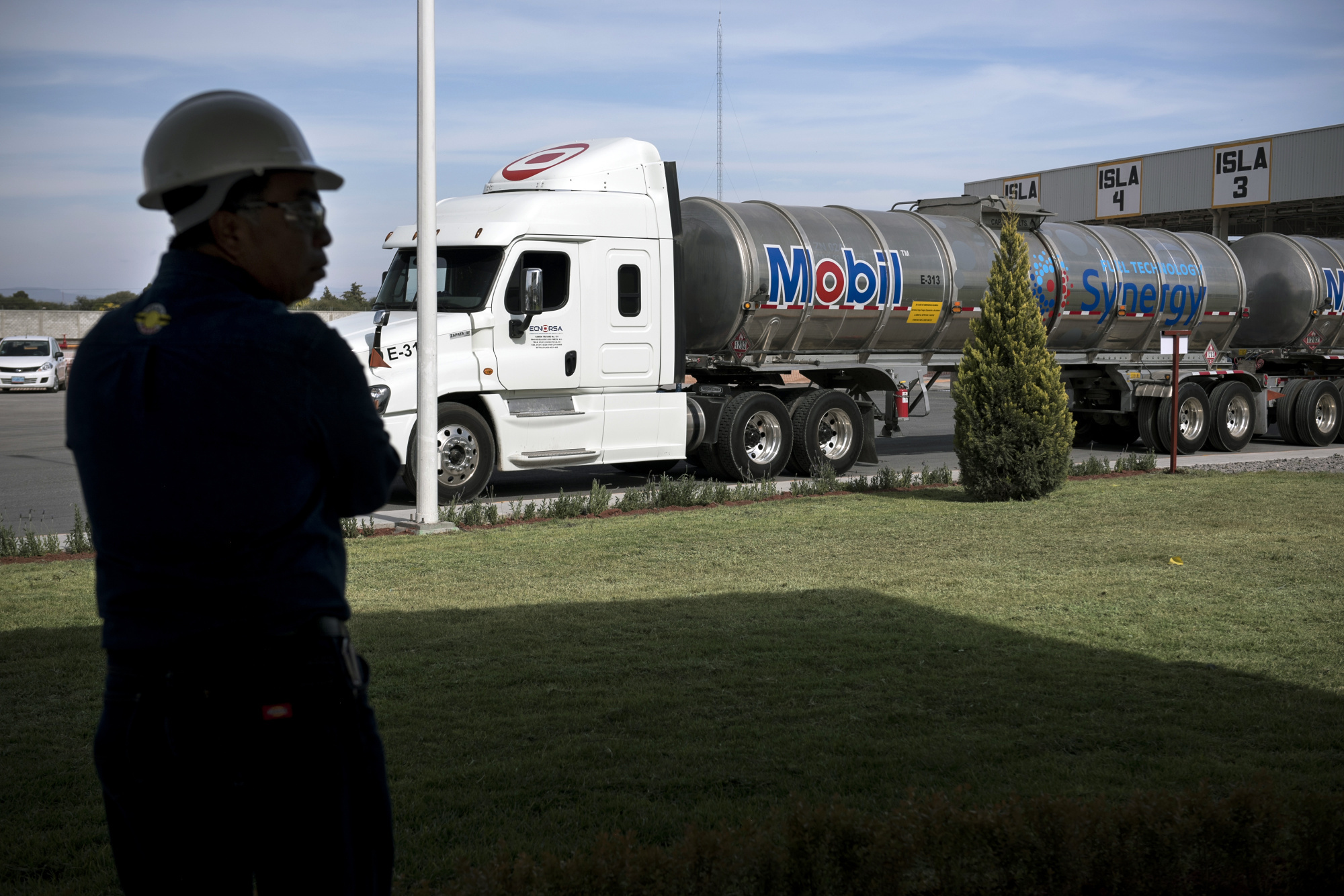 An employee stands in front of a fuel tanker during the unveiling of the Exxon Mobil Corp. fuel terminal in San Jose Iturbide, Mexico, on Wednesday, Dec. 6, 2017. Exxon Mobil Corp. is joining Chevron Corp. and other U.S. refiners to supply the newly free Mexican fuel market. Exxon Mobil indicated Wednesday that it will open 50 service stations by the end of first quarter and invest more than $300 million in Mexico's energy sector. Photographer: Jonathan Levinson/Bloomberg