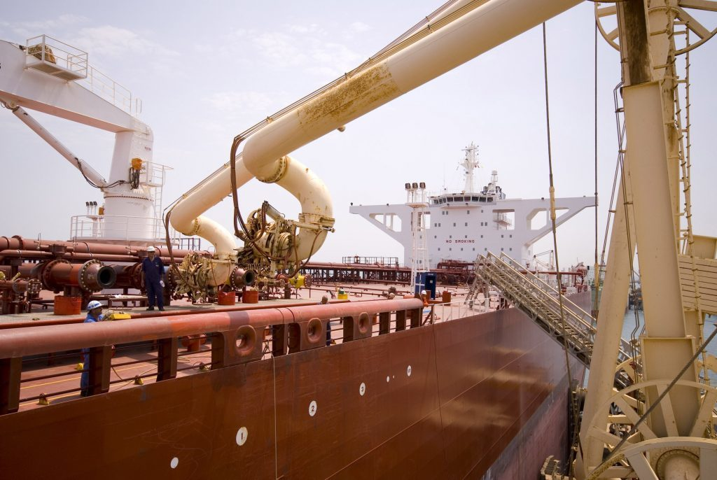 An Iraqi oil worker moves a second loading boom into place on an oil tanker that just arrived to load up with Iraqi crude oil at Al Basra oil terminal in the Northern Arabian Gulf. Photographer: CHARLES CROWELL/Bloomberg